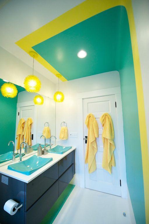 Banheiro branco, azul e amarelo com as cubas, lustres e roupões combinando.