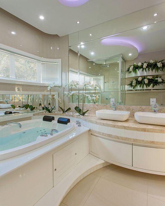 Banheiro duplo com uma hidromassagem para duas pessoas e duas pias.