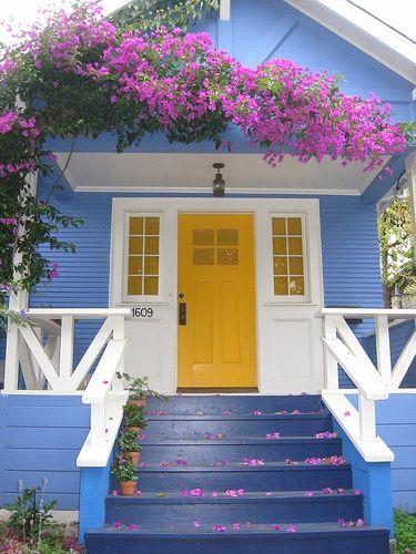 Casa com parede azul e porta amarela.