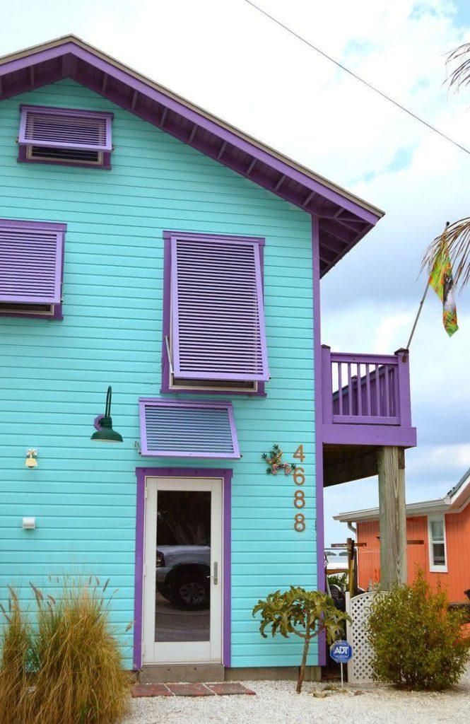Casa com parede azul e porta roxa.