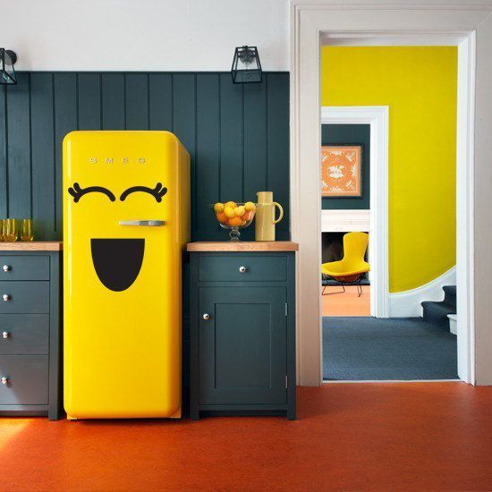 Decoração de cozinha com geladeira retrô amarela com adesivos de olhos e boca.