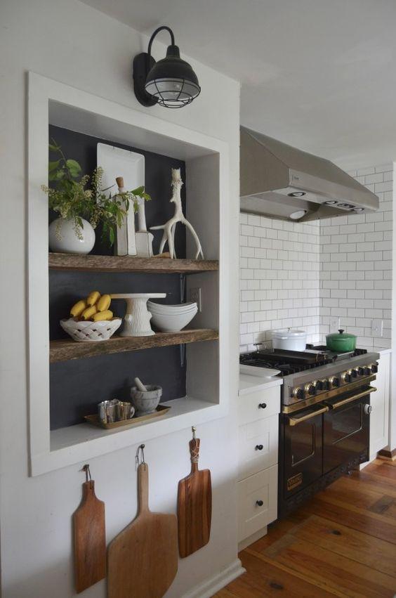 Decoração de cozinha com nichos embutidos, prateleiras de madeira e ganchos para tábuas.