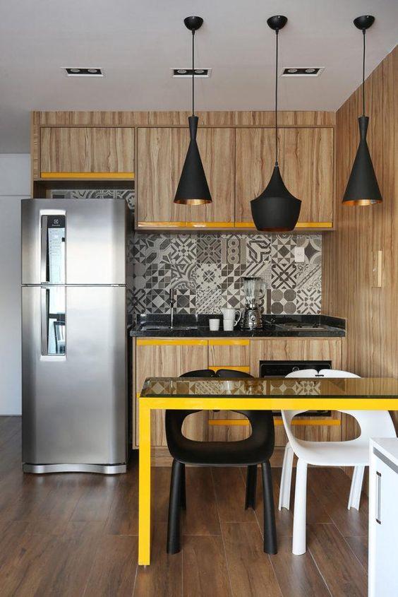 Decoração de cozinha com três lustres em cima da mesa e iluminação embutida no teto.