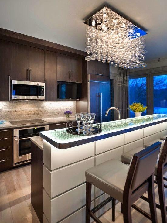 Cozinha com lustre e iluminação embutida embaixo do armário.