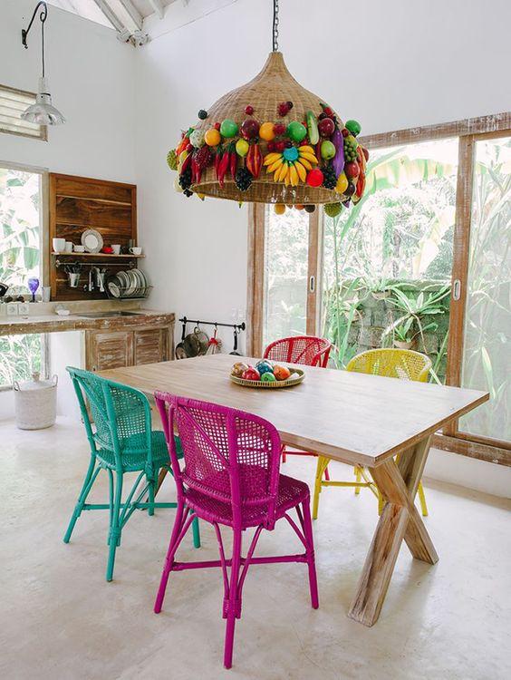 Decoração de cozinha com grande lustre de palha com frutas artificiais.