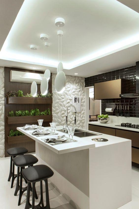 Cozinha moderna com iluminação em sancas e cinco lustres brancos.