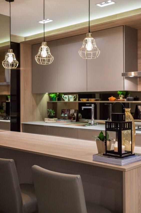 Decoração de cozinha com iluminação embutida e três pequenos lustres suspensos.
