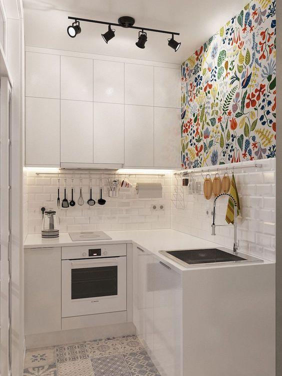 Decoração de cozinha com iluminação receciada a uma das paredes decoradas.