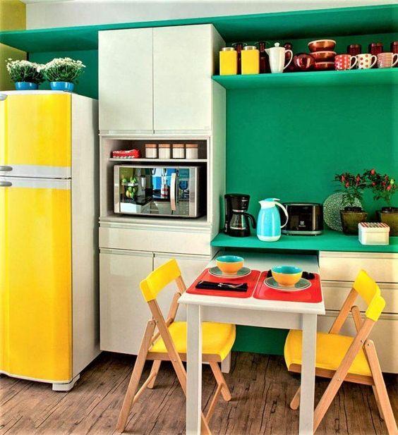 Decoração de cozinha com cadeiras e geladeira amarela.