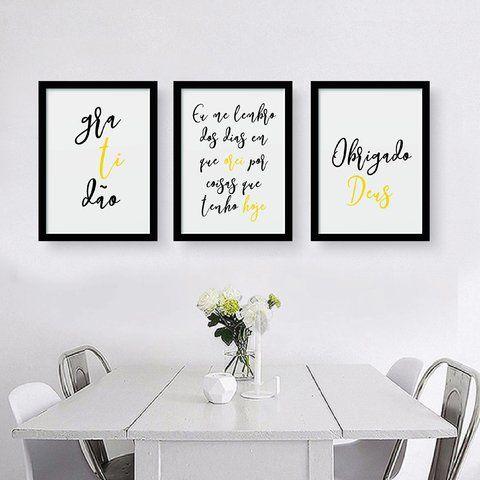 Decoração de cozinha com pequeno vaso de flor na mesa e três quadros pendurados na parede.