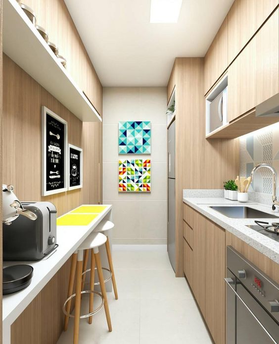 Decoração de cozinha com dois quadros coloridos na parede e dois preto e branco em frente a bancada.