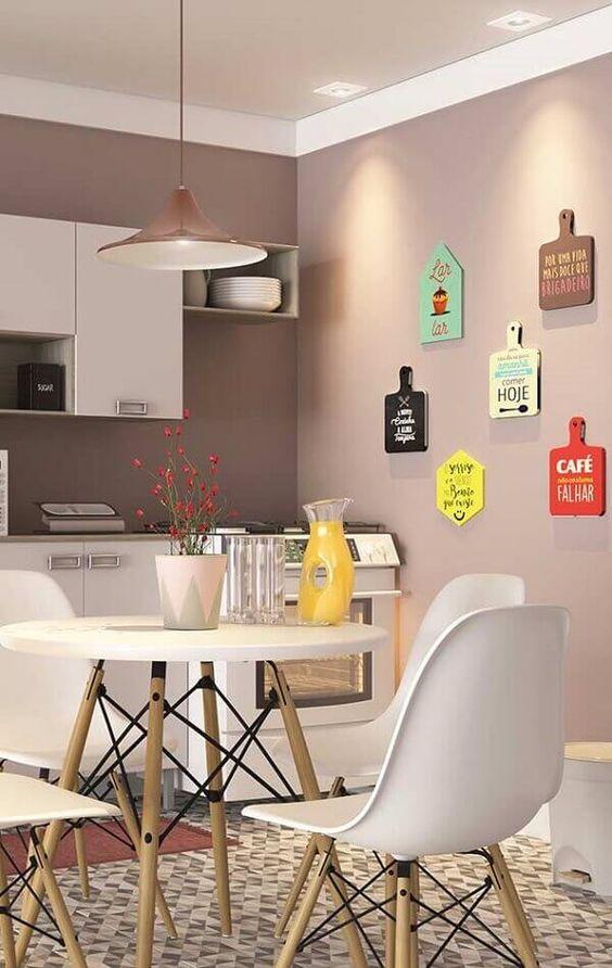 Decoração de cozinha com quadros de vários formatos e cores pendurados na parede.