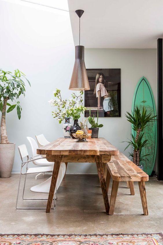 Decoração de cozinha com prancha, grande vasos de planta no chão e pequenos e médios na mesa.