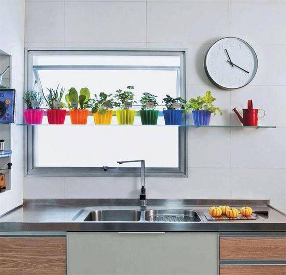 Decoração de cozinha com pequenos vasos coloridos com hortaliças em cima da pia.