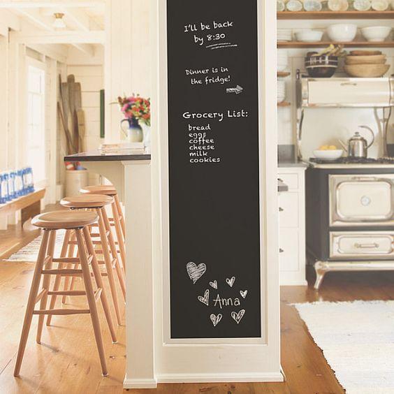 Decoração de cozinha com lousa posta em uma parede de divisão entre a cozinha e o balcão.