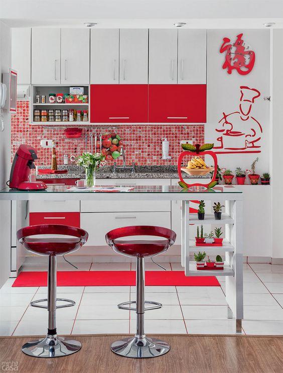 Cozinha com portas de armário, tapete, banquetas, cafeteira e outros itens decorativos em vermelho.