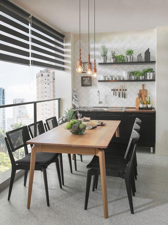 Cozinha decorada com cadeiras pretas de ferro com acento estofado.