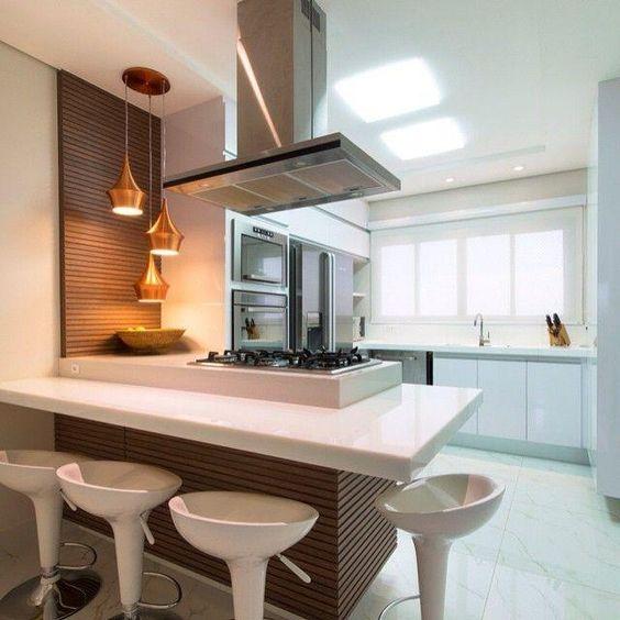 Cozinha branca com quatro banquetas modernas da mesma cor.
