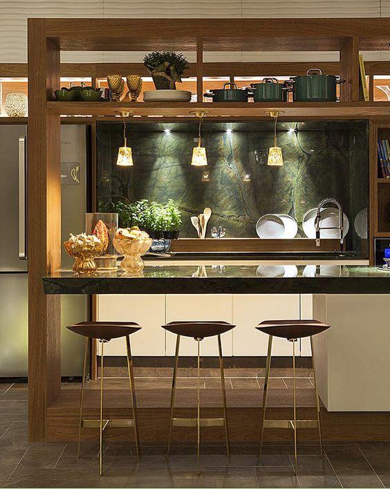 Decoração de cozinha com bancos de pés finos e da mesma cor que a estrutura amadeirada da cozinha.