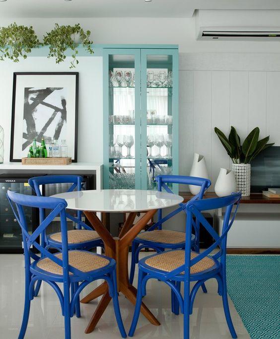 Decoração de cozinha com quatro cadeiras azuis com acento trançado.