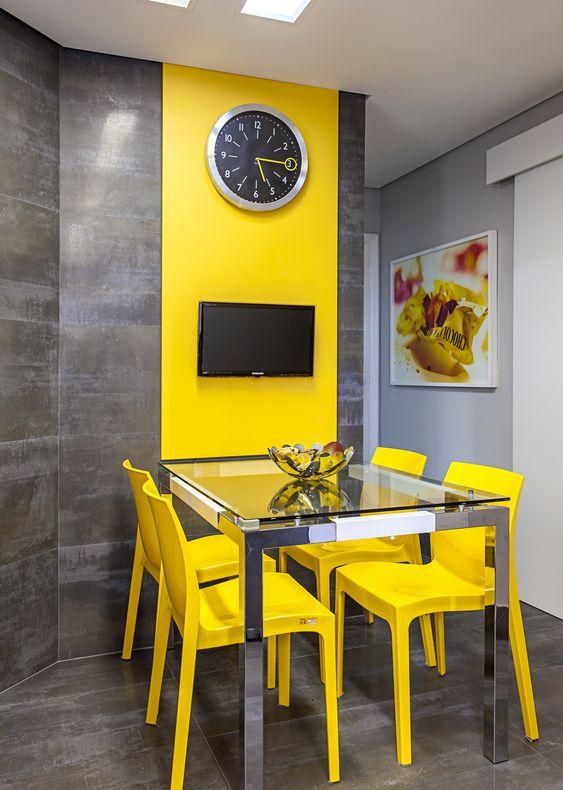 Cadeiras amarelas no mesmo tom da parede.