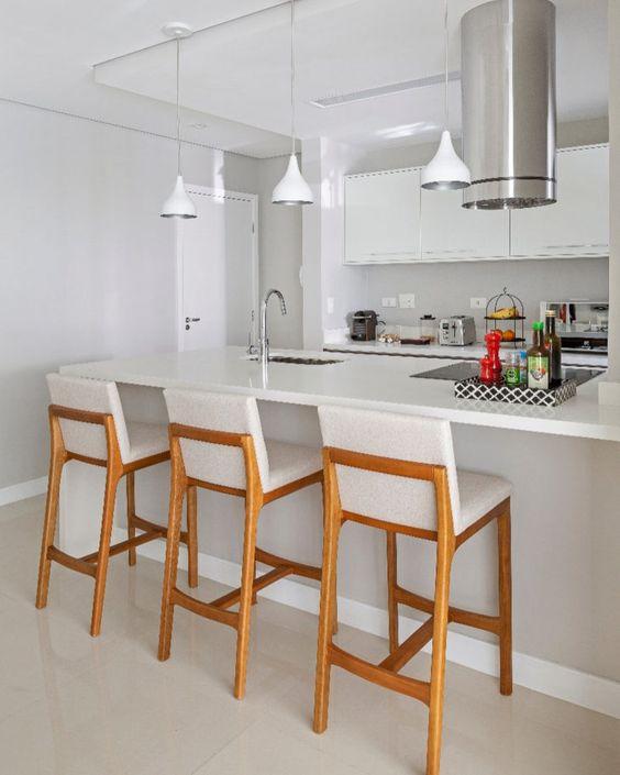 Decoração de cozinha com três banquetas de madeira com estofados brancos.