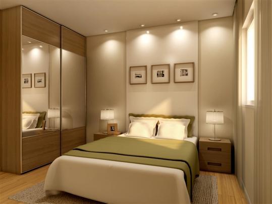 Decoração de apartamento pequeno com espelhos no guarda-roupa, mesinhas de cabeceira e quadros no quarto.
