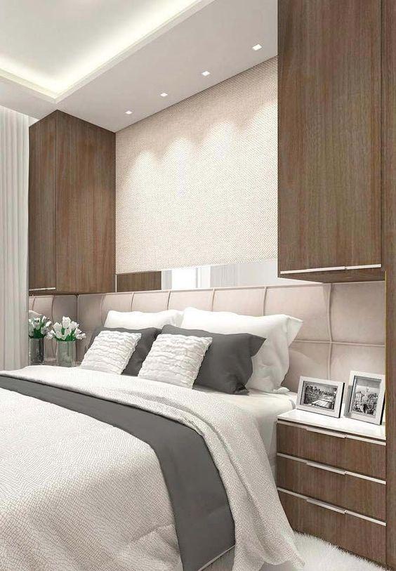 Decoração de apartamento pequeno com armários nas laterais da cama de casal.