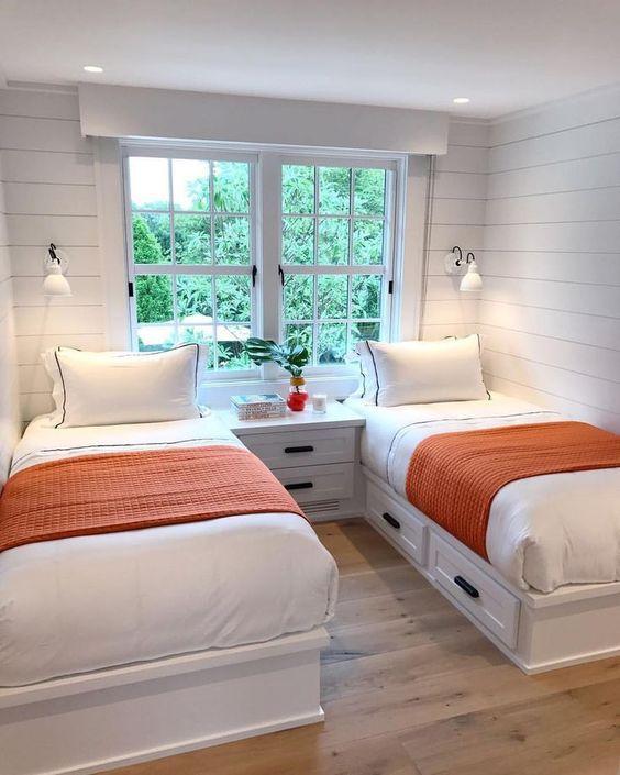 Quarto todo branco com duas camas e detalhes laranja.
