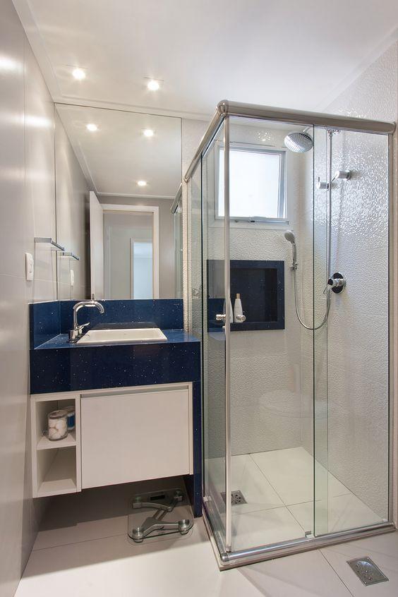 Banheiro branco com pia e nicho azuis.