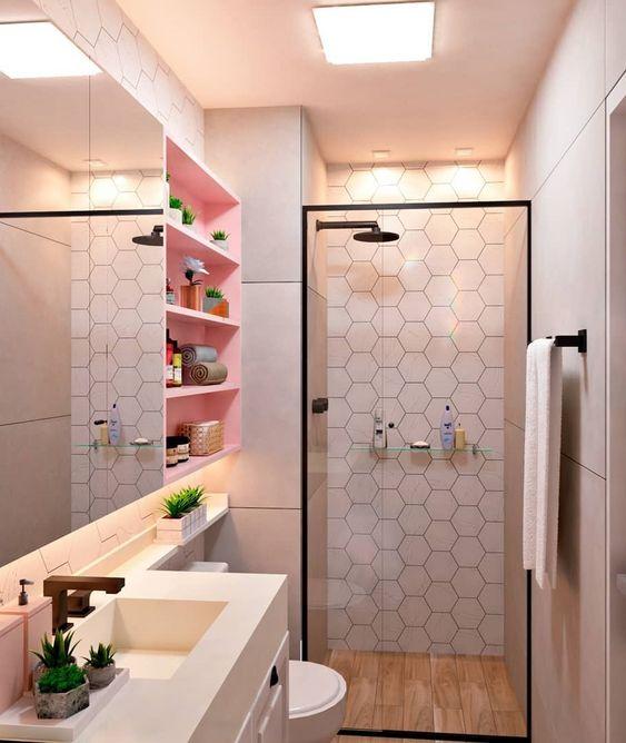 Banheiro pequeno rosa com prateleiras organizadoras.