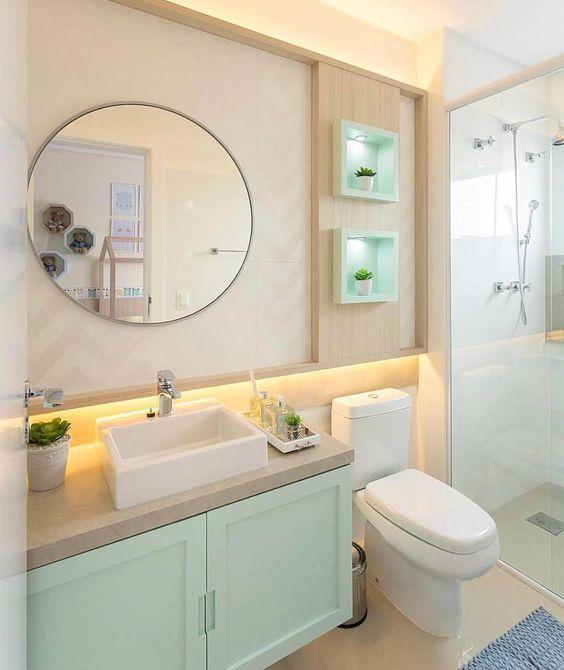 Decoração de banheiro pequeno com espelho redondo e nichos iluminados com pequenos vasos de planta.