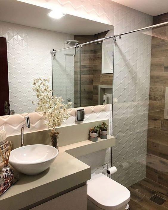 Banheiro decorado com cuba branca e redonda e vasos de flor e suculentas.
