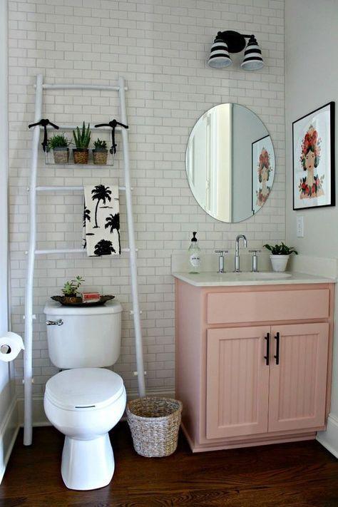 Decoração de apartamento pequeno com quadros e plantas no banheiro.