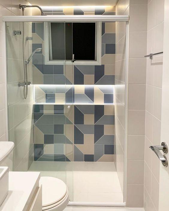 Banheiro pequeno decorado com uma parede colorida com nicho iluminado.