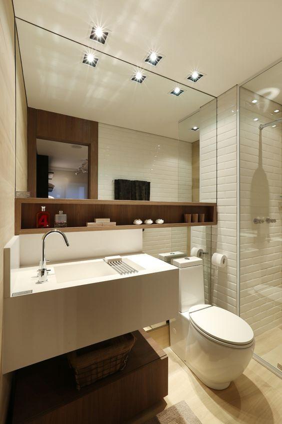 Decoração de apartamento pequeno com espelho grande no banheiro e nicho organizador de madeira.
