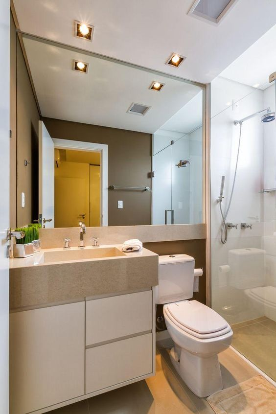 Banheiro decorado com grande espelho e luzes de LED embutidas no teto.