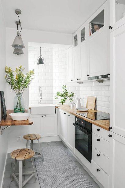 Cozinha de apartamento pequena com armários brancos e pequena prateleira que serve de mesa.