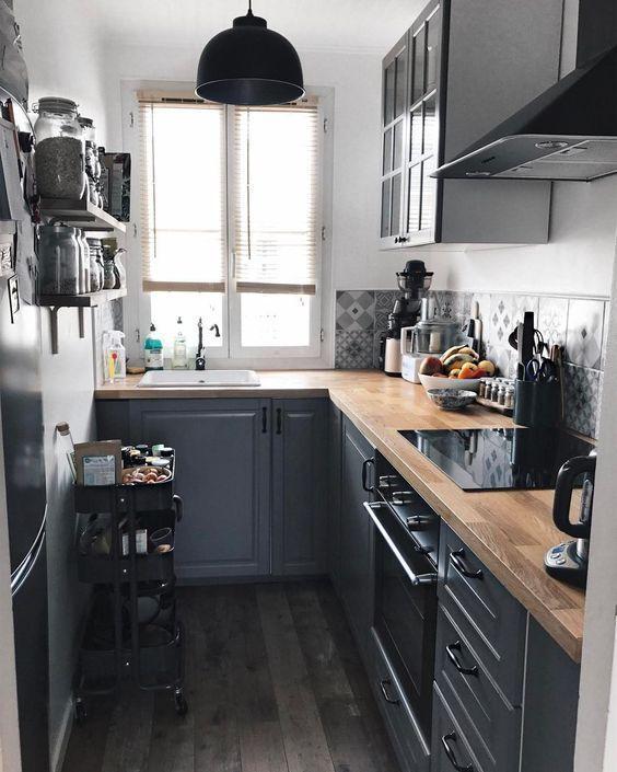 Decoração de apartamento pequeno com cozinha com fruteira e lustre pretos.
