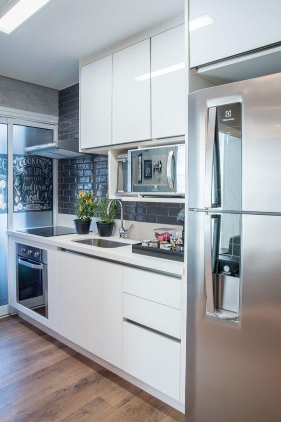 Cozinha com móveis planejados brancos.