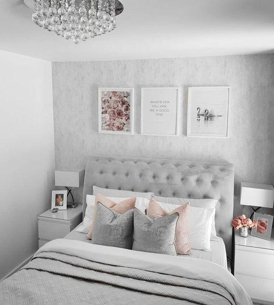 Quarto pequeno decorado com almofadas, quadros e mesinhas de cabeceira com abajurs.