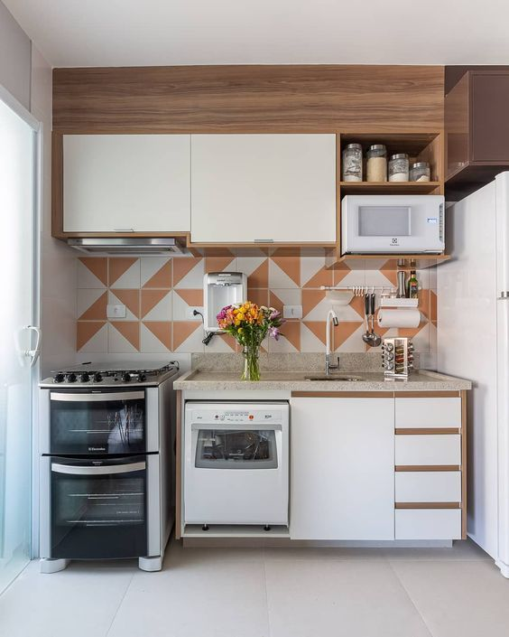 Cozinha com móveis neutros e revestimento colorido.