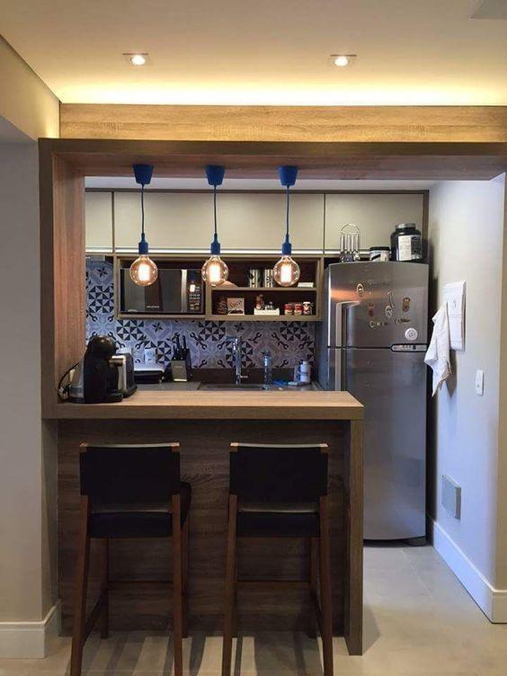 Cozinha decorada com luminárias suspensas e balcão de madeira.