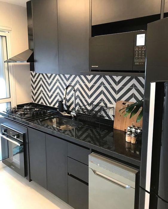 Cozinha toda preta com revestimento preto e branco.