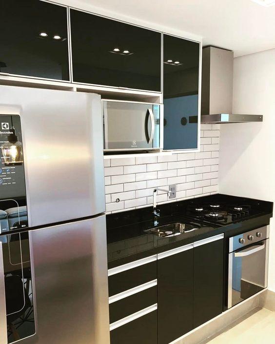 Cozinha decorada com armários pretos.