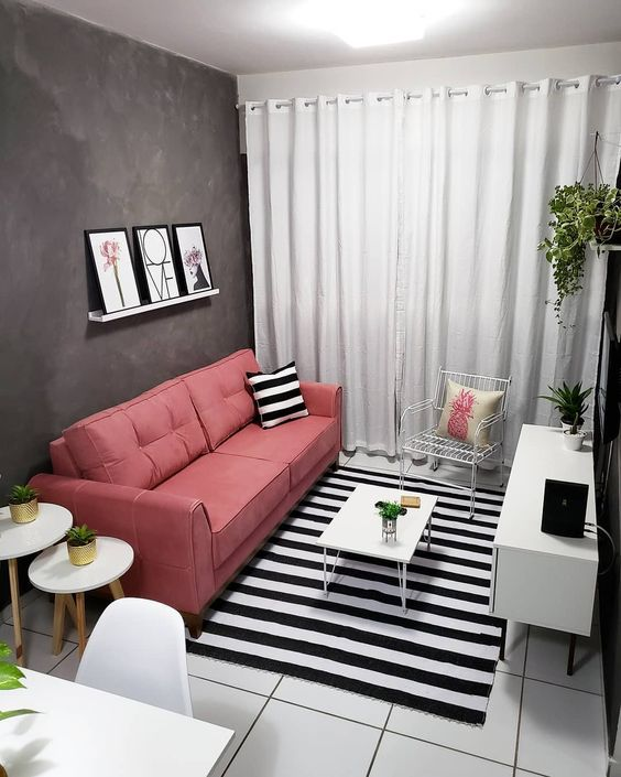 Sala decorada com almofada e tapete listrados em preto e branco.