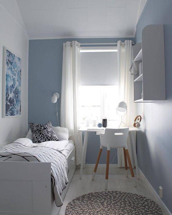 Quarto simples com decoração branca e azul.