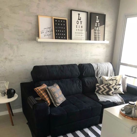 Sala decorada com prateleira cheia de quadros, e sofá com almofadas coloridas.