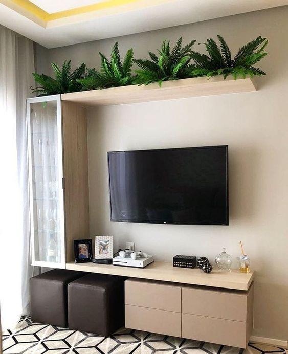 Decoração de sala pequena com plantas, cristaleira e puffs.
