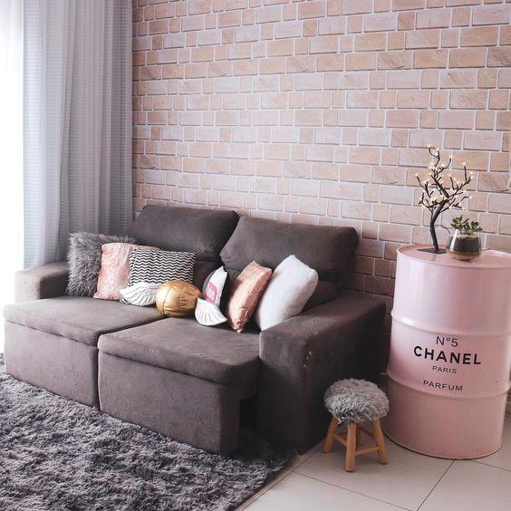 Decoração de apartamento pequeno com sala cheia de almofadas de cores, tamanhos e texturas diferentes.